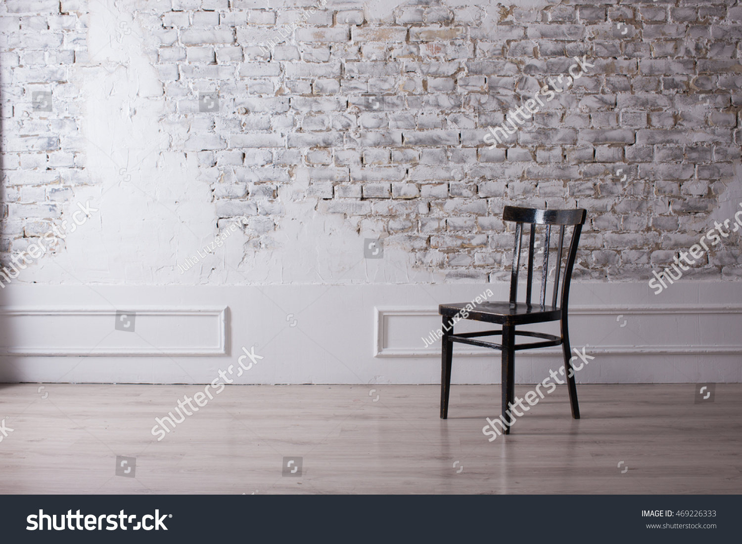 Decorative White Brick, A White Wall And A Black Chair In A Spacious Room,