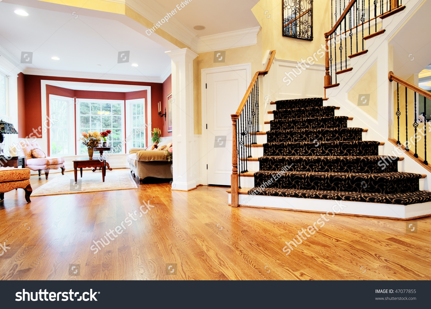 Open Foyer And Living Room : Open entryway with wood floor and staircase view of