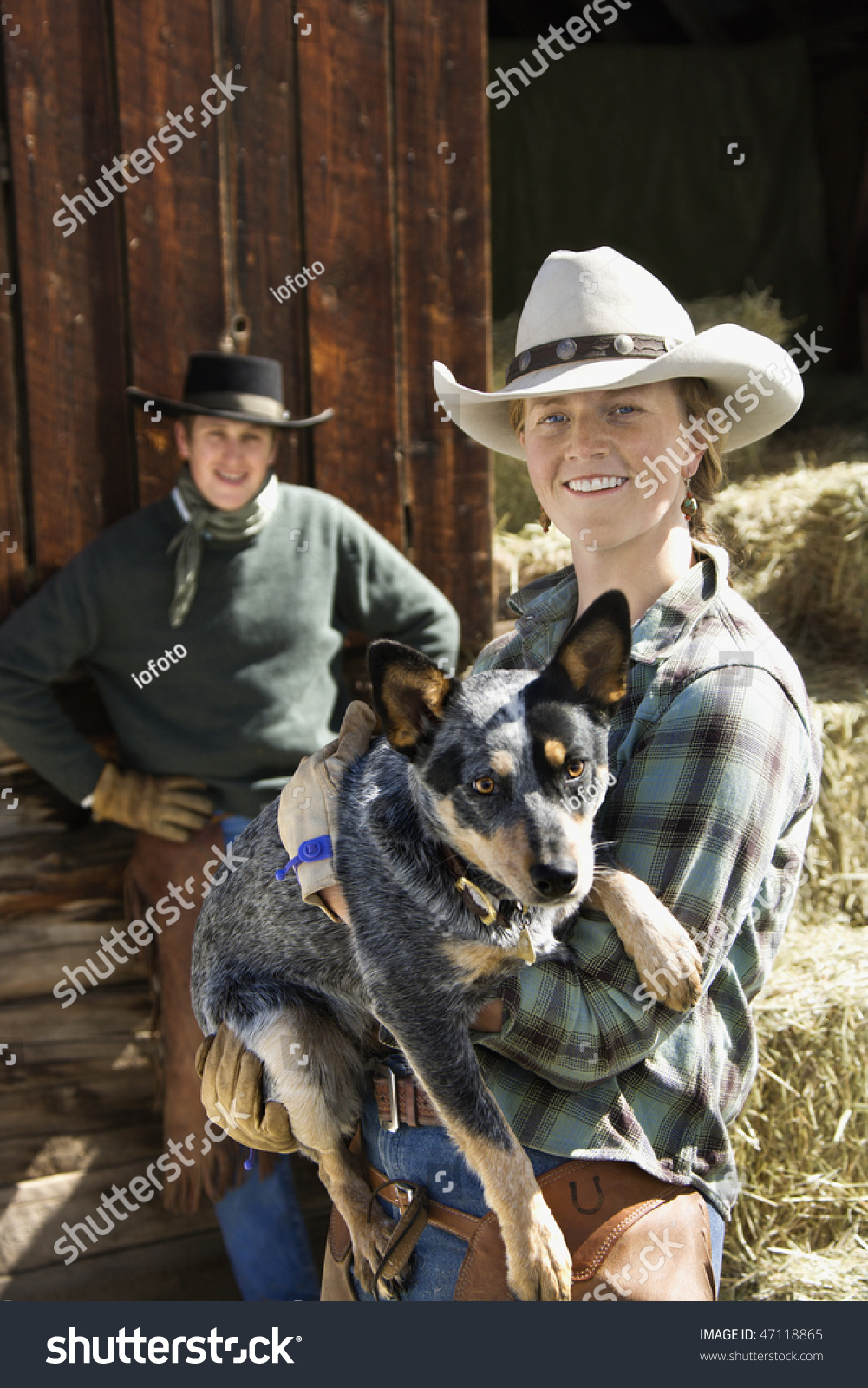 c6f9ade24d64f Attractive young woman wearing a cowboy hat and holding an Australian  Shepherd. A young man is standing in the background. Vertical shot. - Image