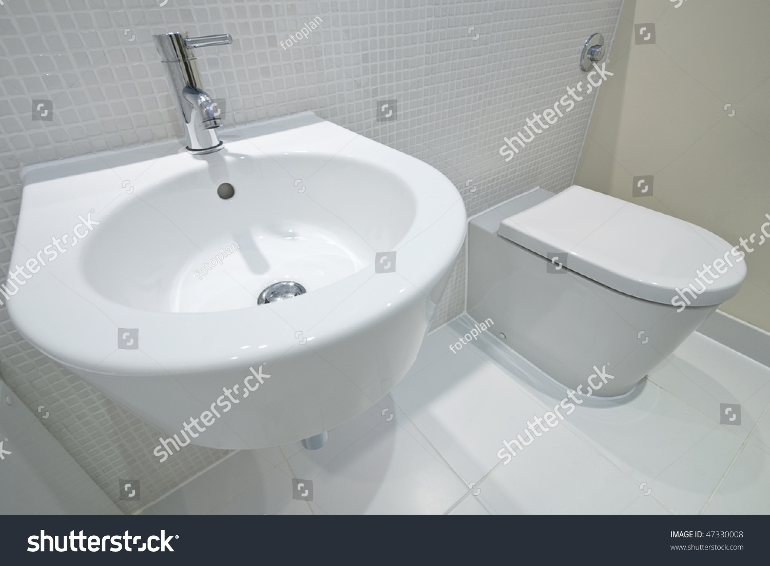 Bathroom Detail With Hand Wash Basin And Toilet With Mosaic Tiles