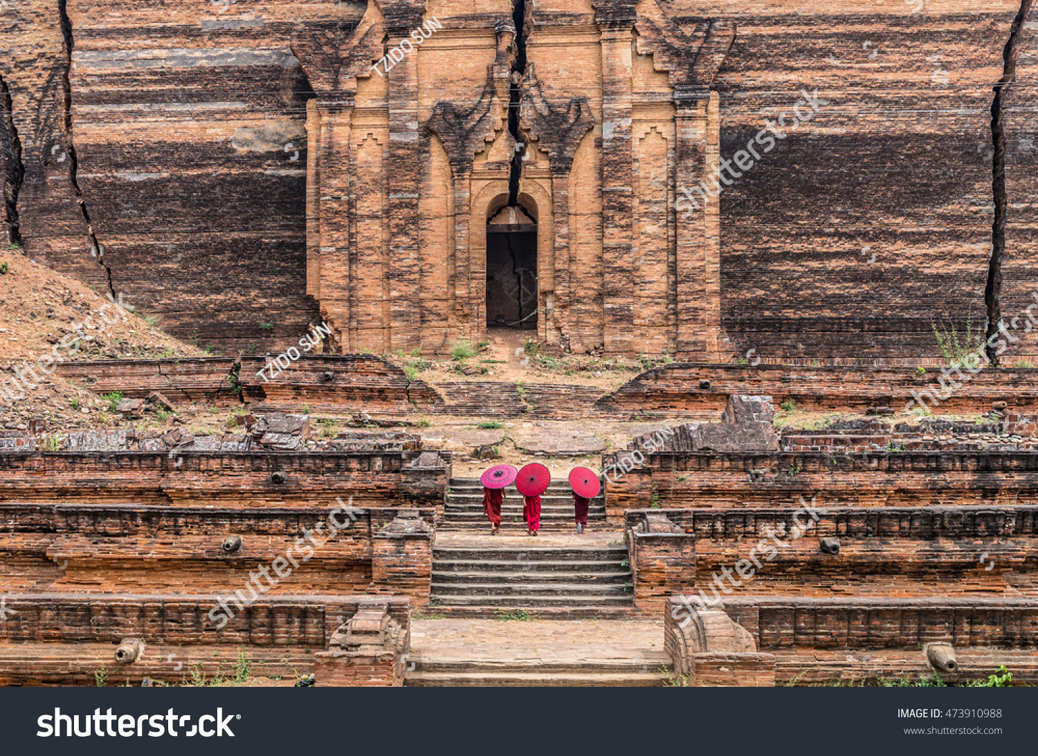 Three Buddhist novice are walking and holding the red umbrella at Mingun Pahtodawgyi bagan mandalay myanmar public domain