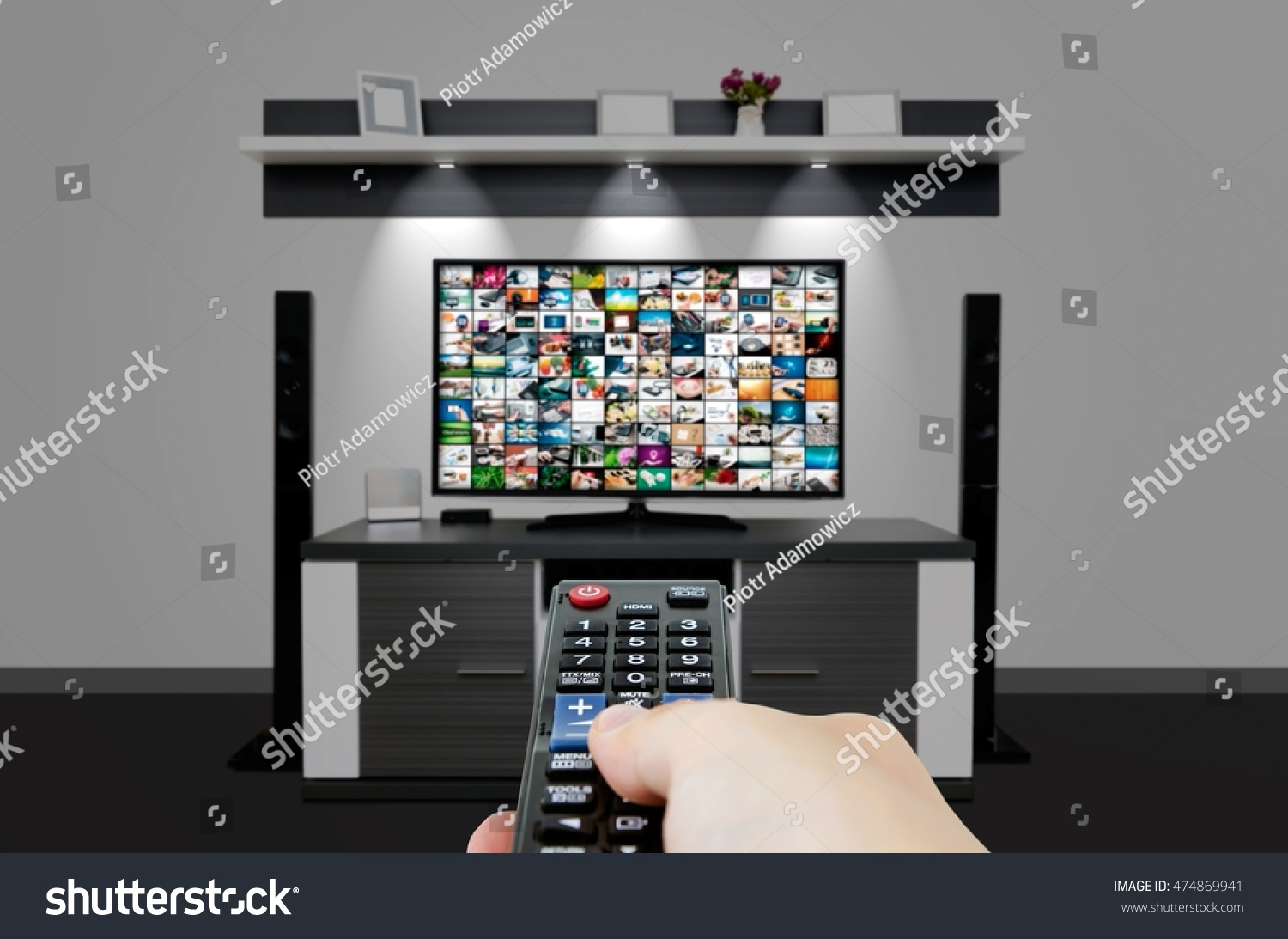 Watching television in modern TV room Hand holding remote control