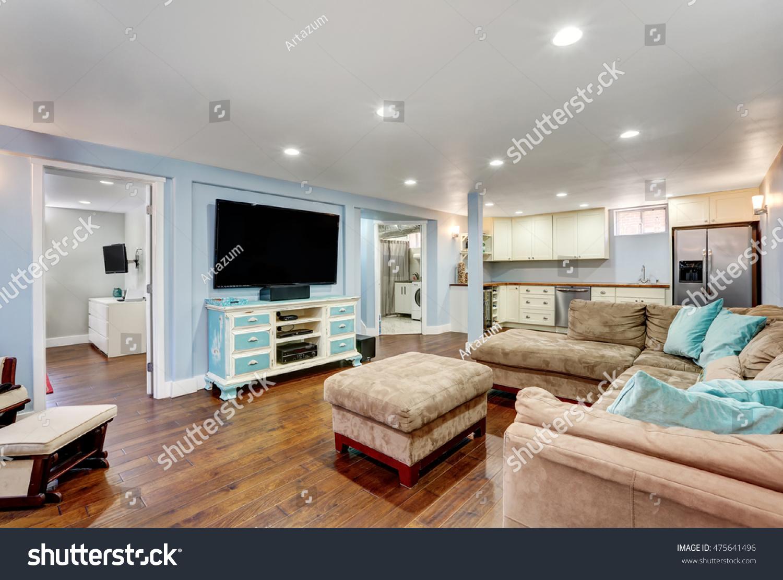 Pastel Blue Walls In Basement Living Room Interior With Open Floor Plan.  Large Corner Sofa