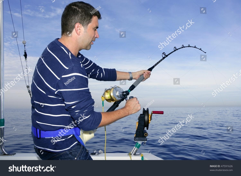 Angler fisherman fighting big fish rod and reel saltwater for Big fishing pole
