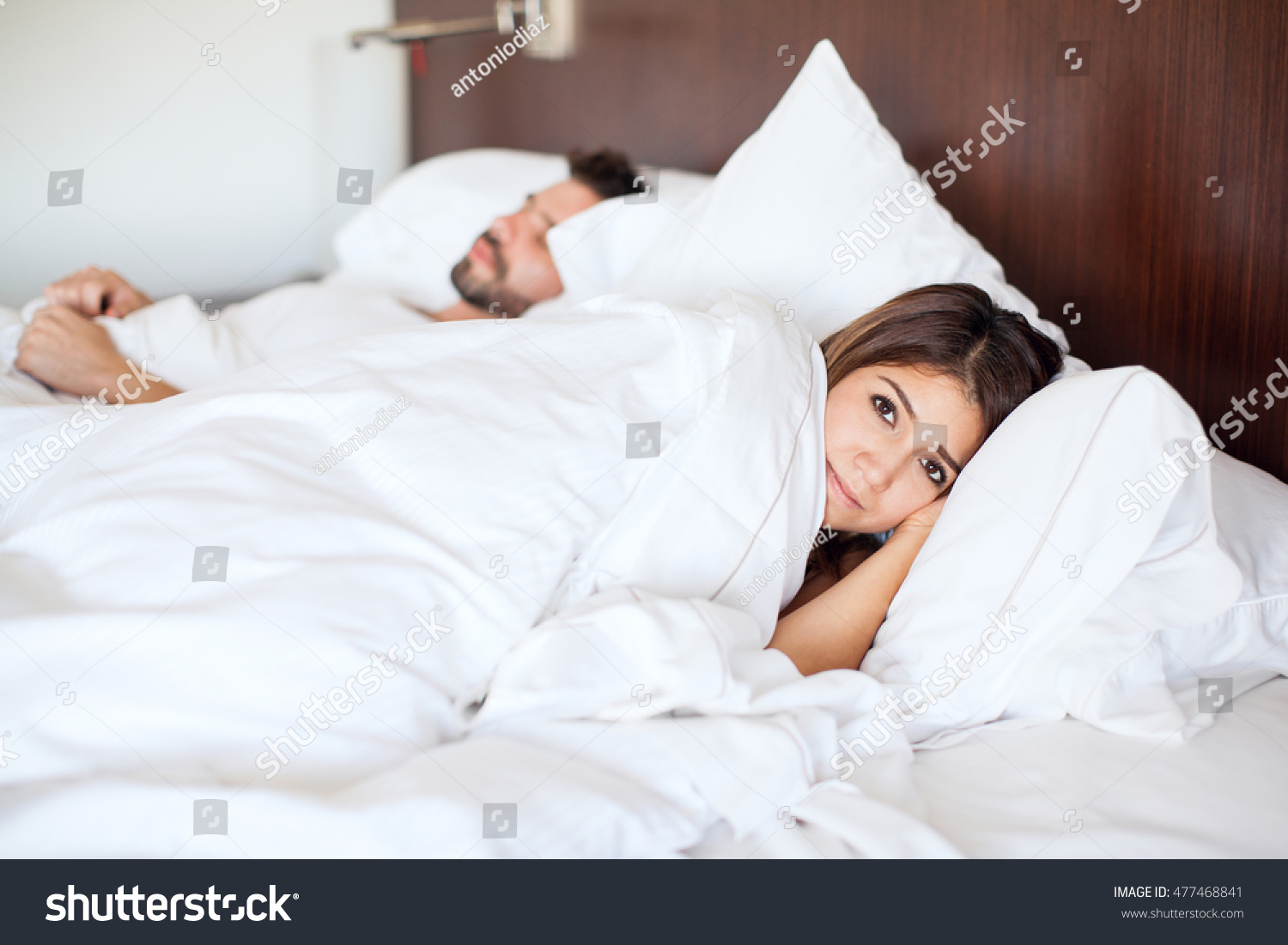 portrait beautiful brunette staying awake while stock photo portrait of a beautiful brunette staying awake while her partner sleeps next to her