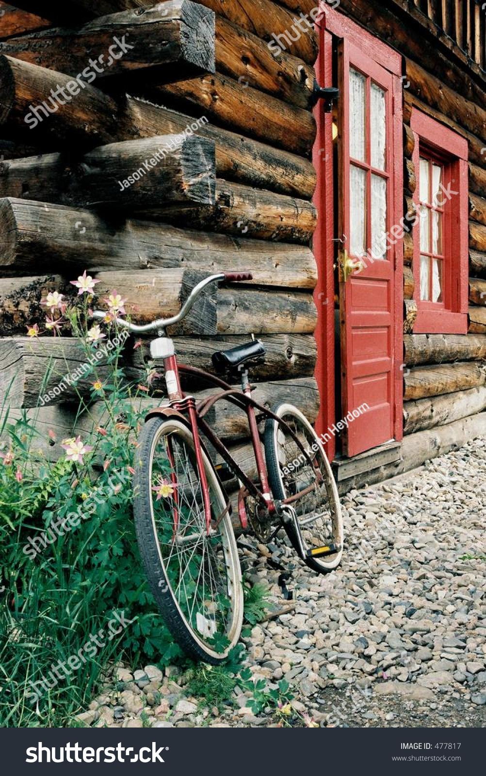 Vintage cruiser bicycle leaning against log imagen de for Caseta guarda bicicletas