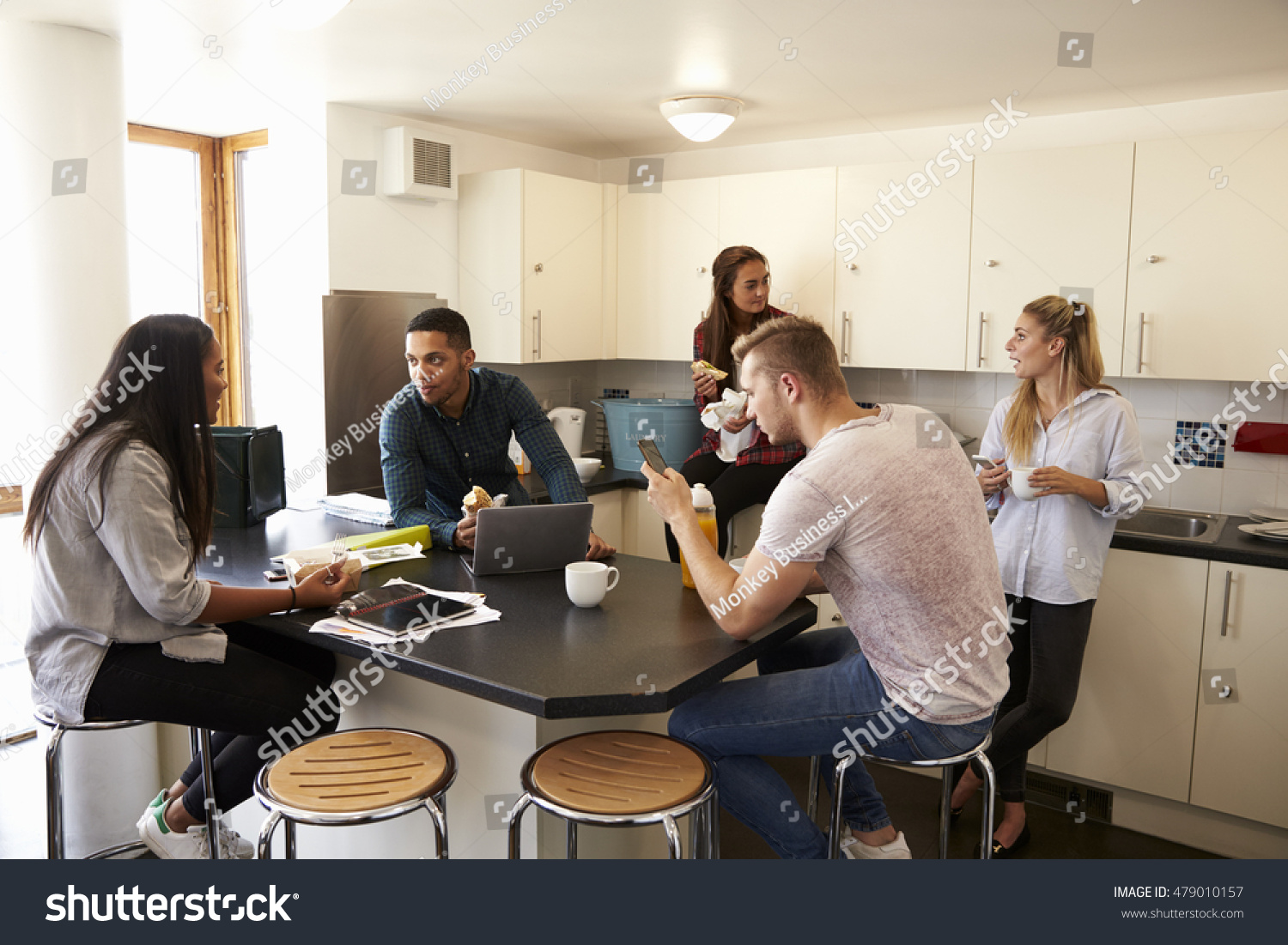 students relaxing in kitchen of shared accommodation - Shared Kitchen