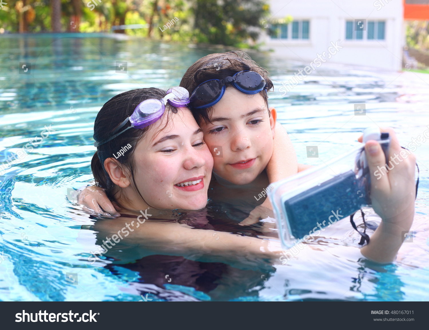 teen siblings brother and sister take photos with underwater cover camera  close up portrait in open