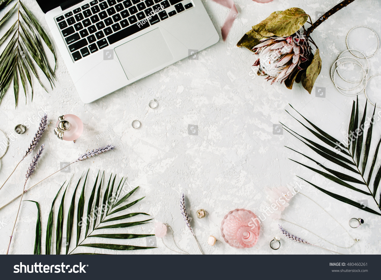 flat lay feminine home office workspace with laptop proteus flower necklace palm branches accessories e