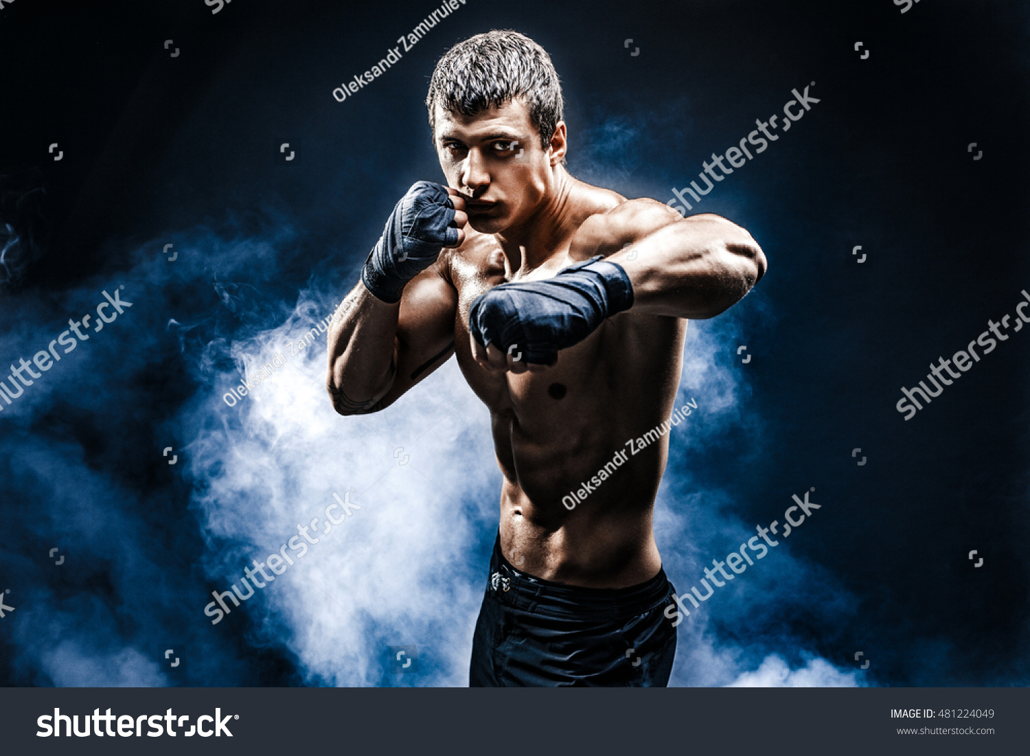 Muscular kick-box or muay thai fighter punching in smoke