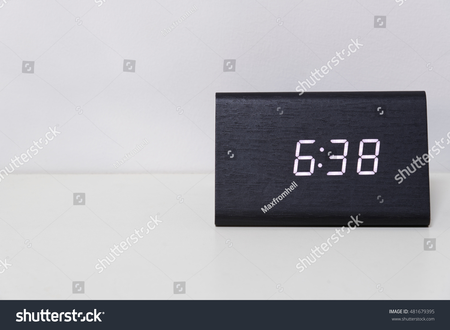 Black digital clock on a white background showing time 6:38 (six hours thirty-eight minutes)