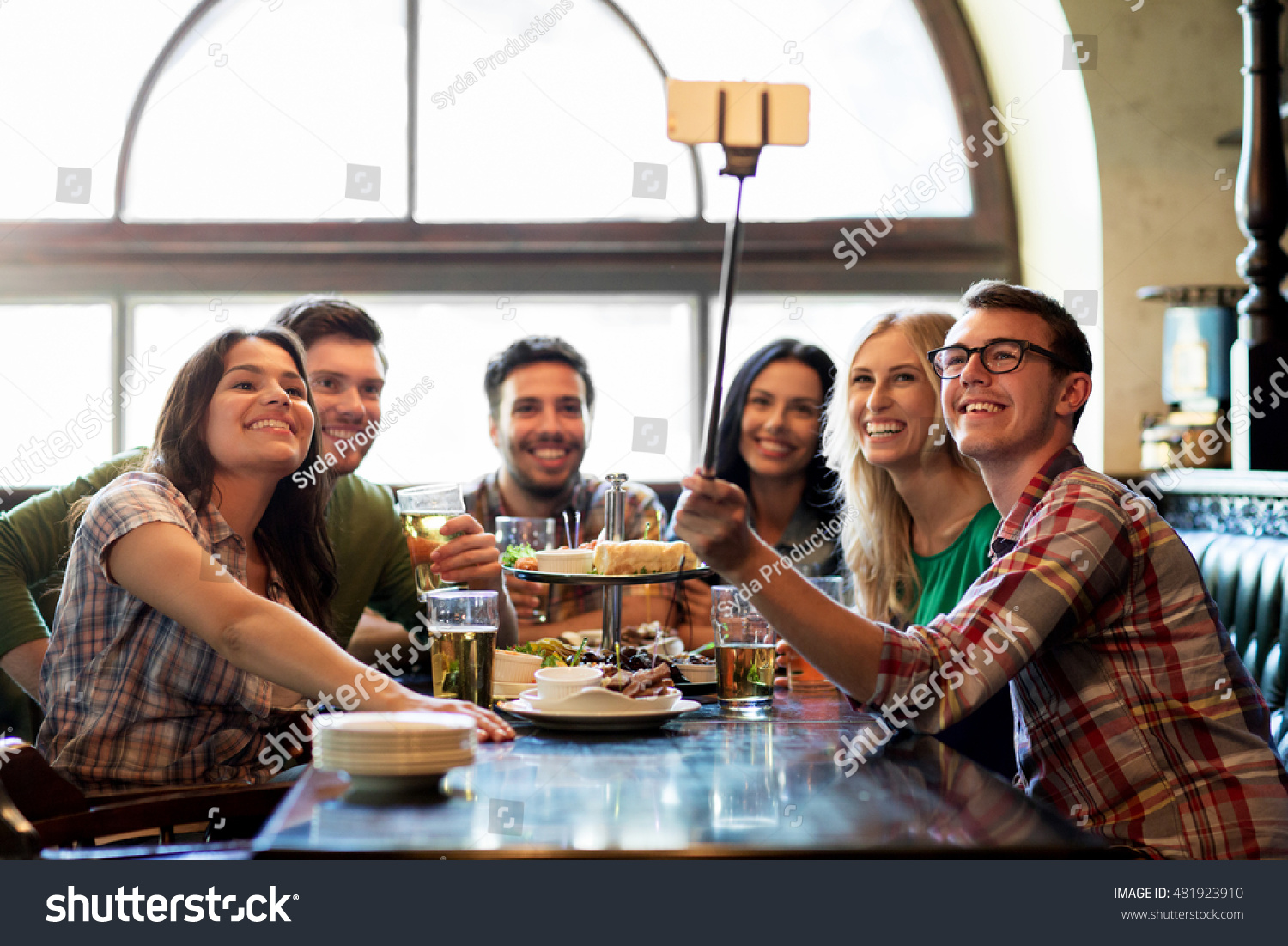 people leisure friendship and technology concept happy friends taking picture by smartphone selfie stick drinking beer and eating snacks at bar or pub