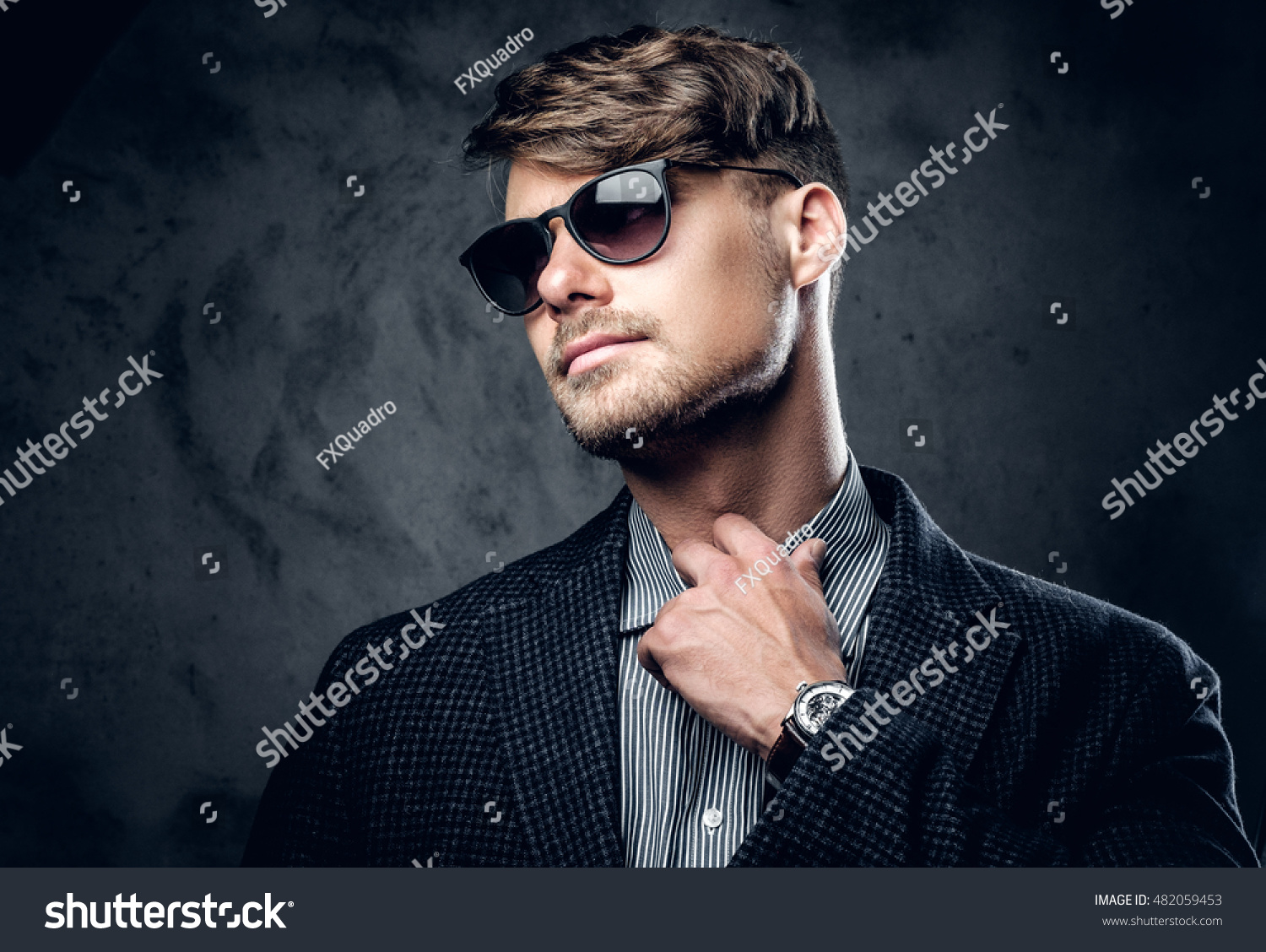 23a57db91adf Fashionable studio portrait of male in a suit and sunglasses on grey  background.