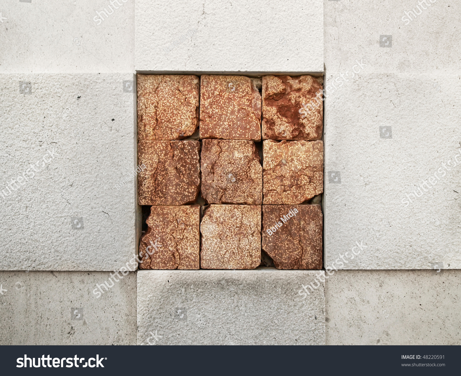 Red Granite Cube : Nine red granite cubes embedded in white marble wall stock