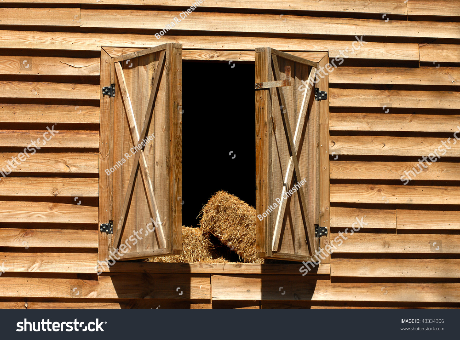 Wooden Barn Has Loft Doors Open With Bales Of Hay Ready