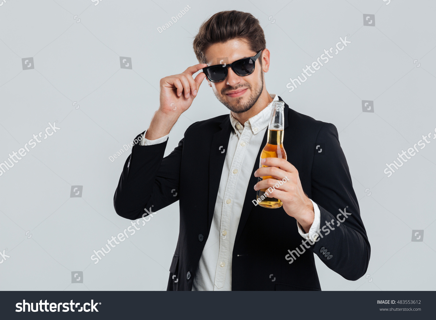 c84b614ebbe1 Smiling stylish man in sunglasses and black suit holding beer bottle over grey  background