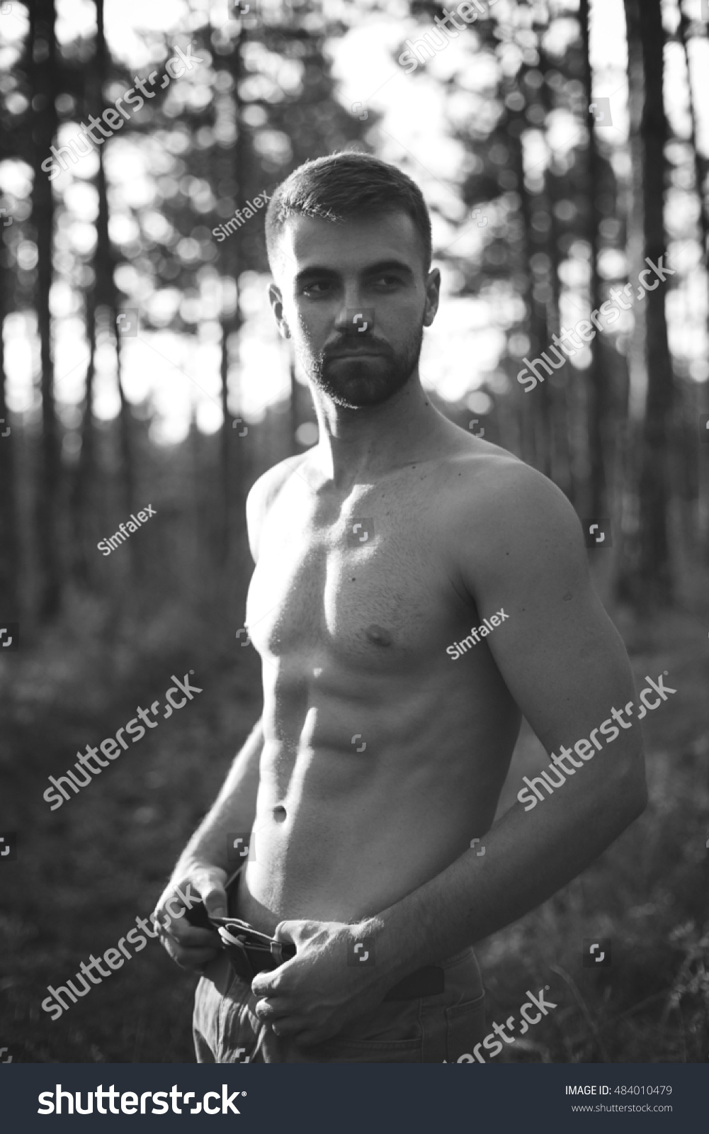 Black and white portrait of a beautiful shirtless man in jeans in natural outdoor setting
