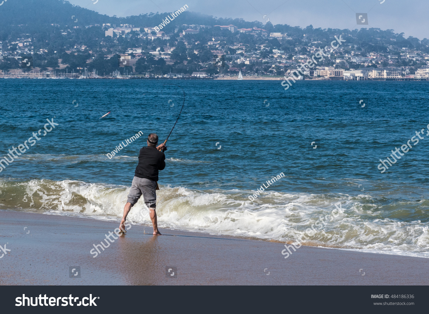 Seaside, California - September 15, 2016: A man enjoys an active lifestyle fishing in the surf along the sandy shore of the beach in Seaside, along the coast of the Monterey Bay in central California.