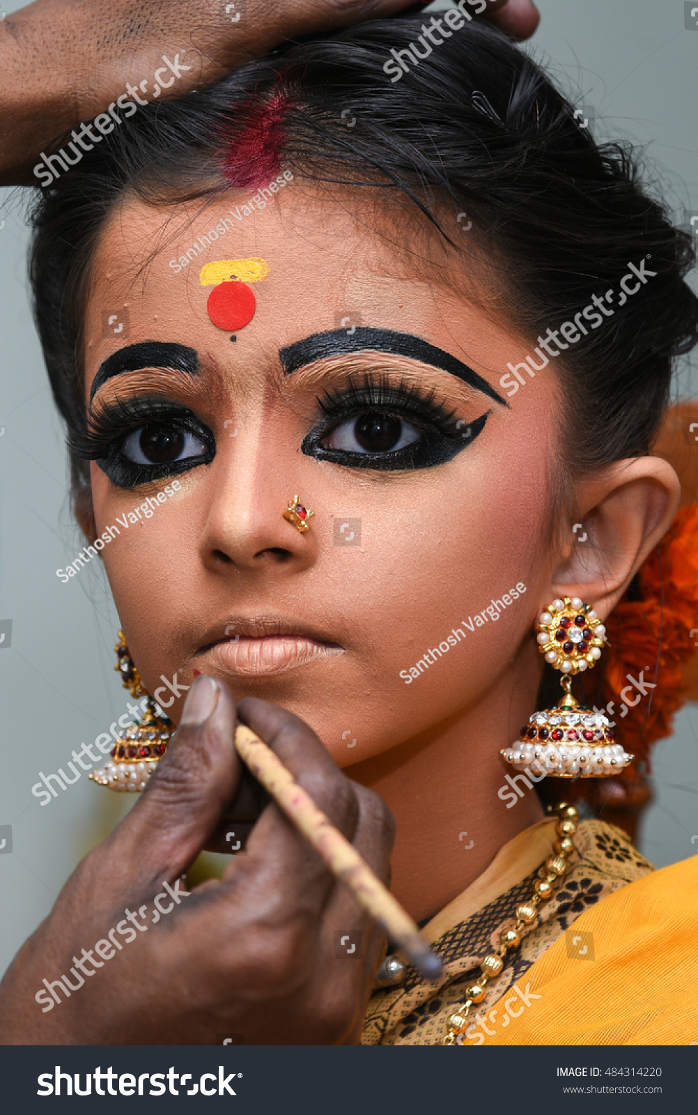 Makeup artist applies lipstick for beautiful young Indian girl/woman/kid/child wearing