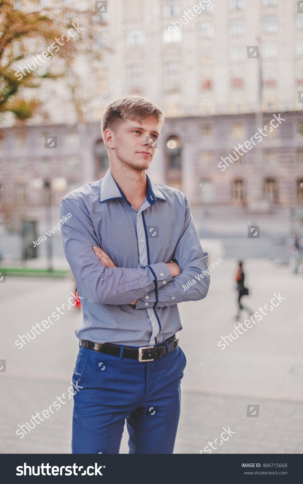 Beautiful young attractive cheerful man model blonde in classic suit  standing amidst the city center street