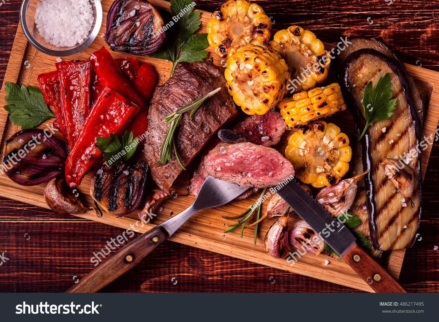 Grilled steak and vegetables on cutting board, top view. #486217495