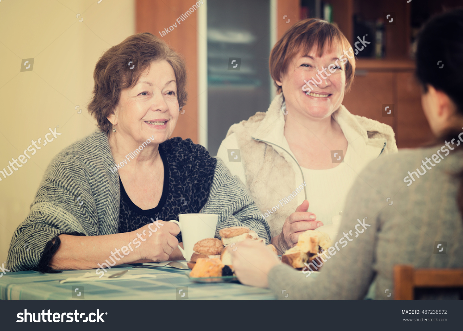 Mature women with adult girl drinking tea and chatting indoors