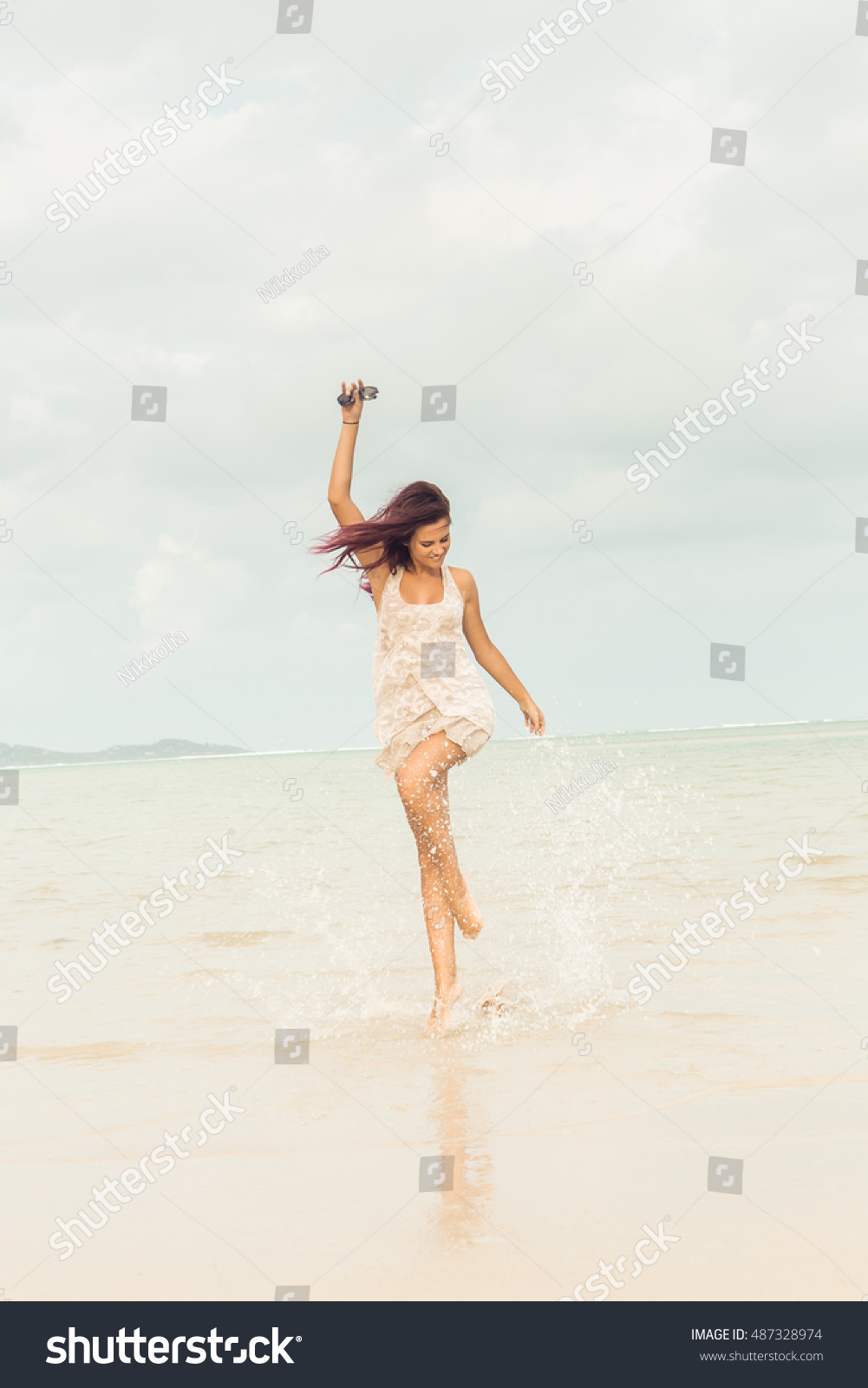 629b91164c Sexy woman in light summer dress on rock beach with big stones at the sea  ocean