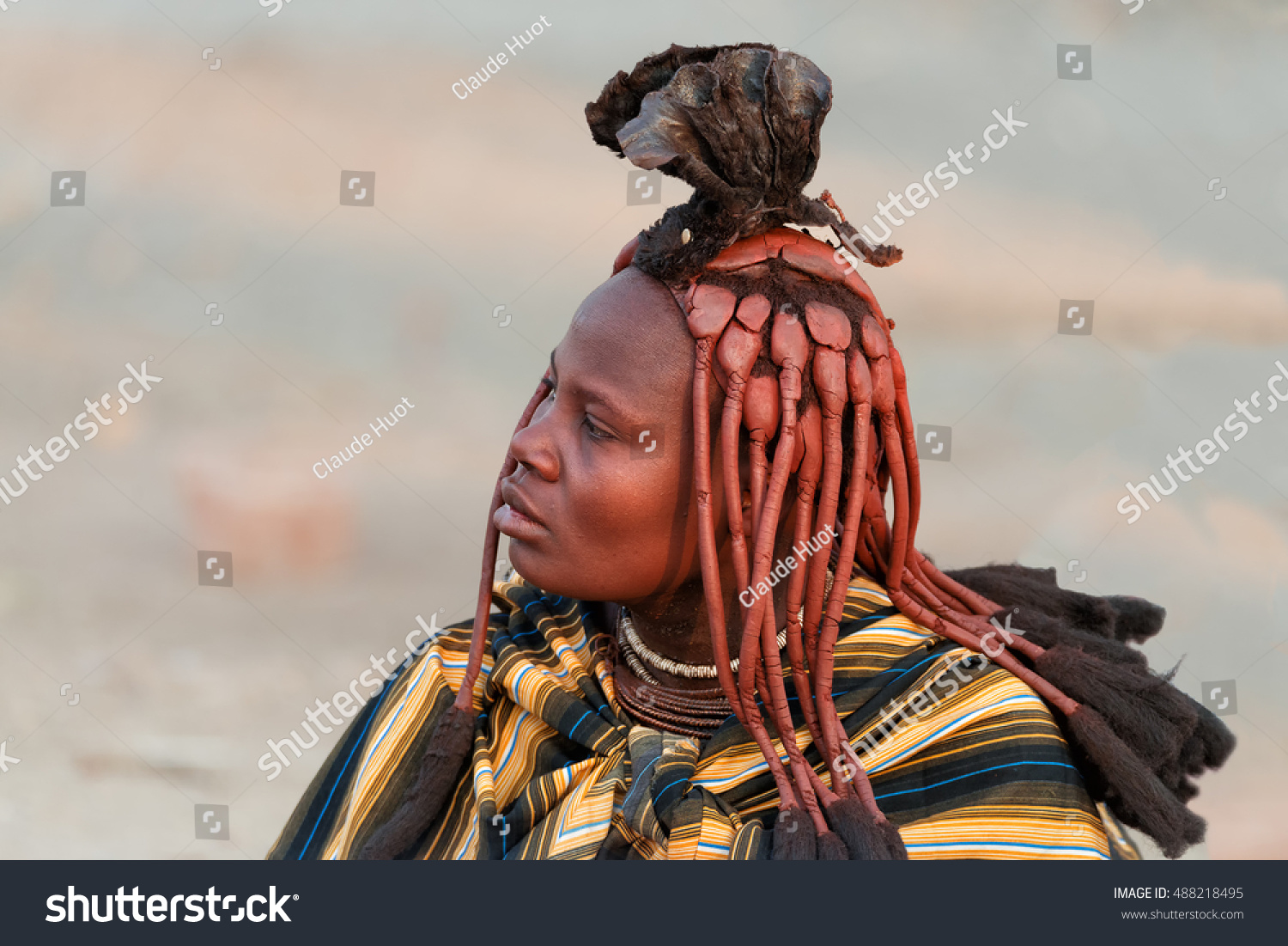 OMBIKA, NAMIBIA - SEPTEMBER 5, 2016:  Himba woman with traditional hairstyle and red skin poses for money. The Himba women from Northern Namibia apply a red paste to their hair and body.