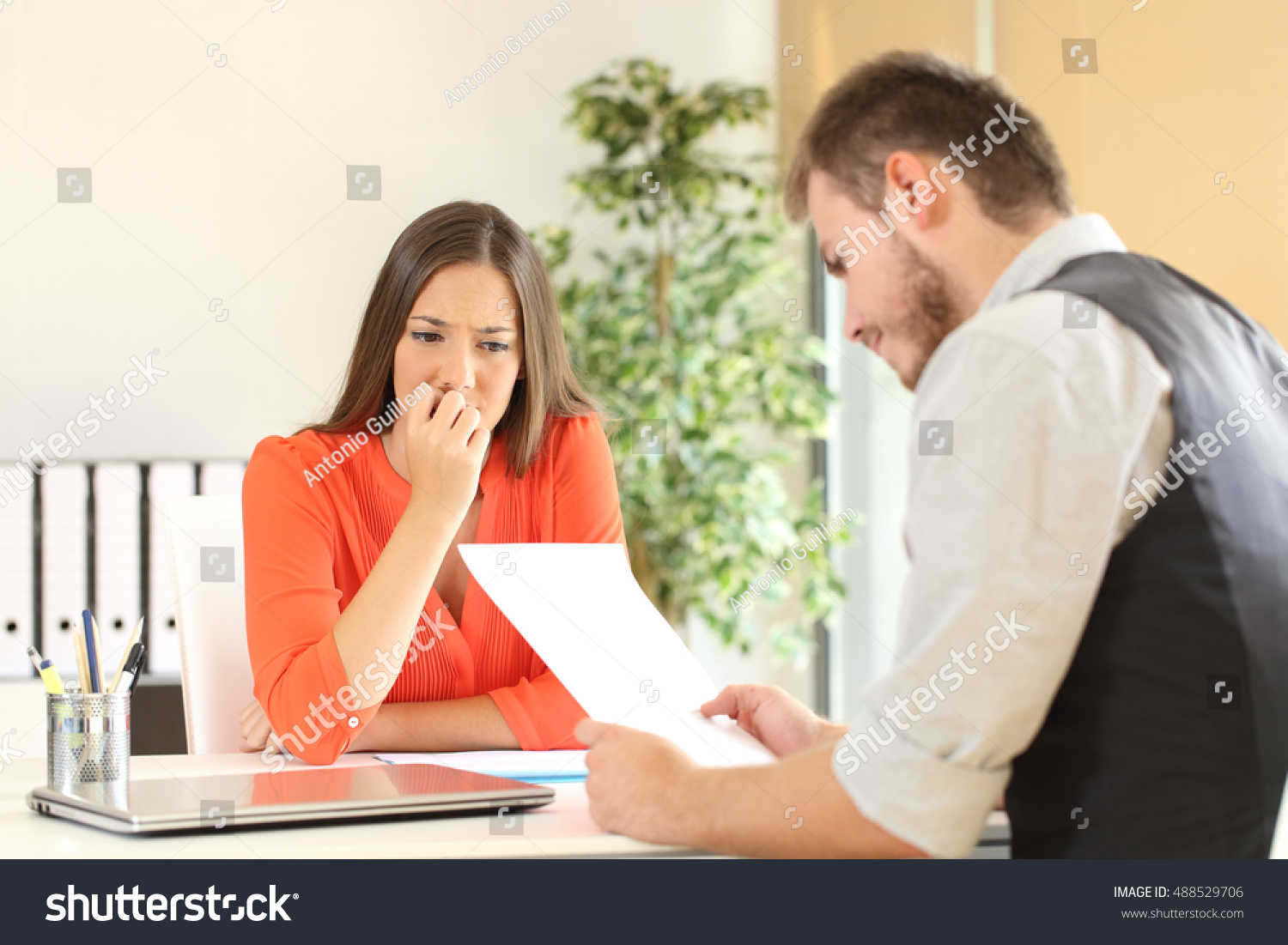 nervous woman looking manager reading her stock photo 488529706