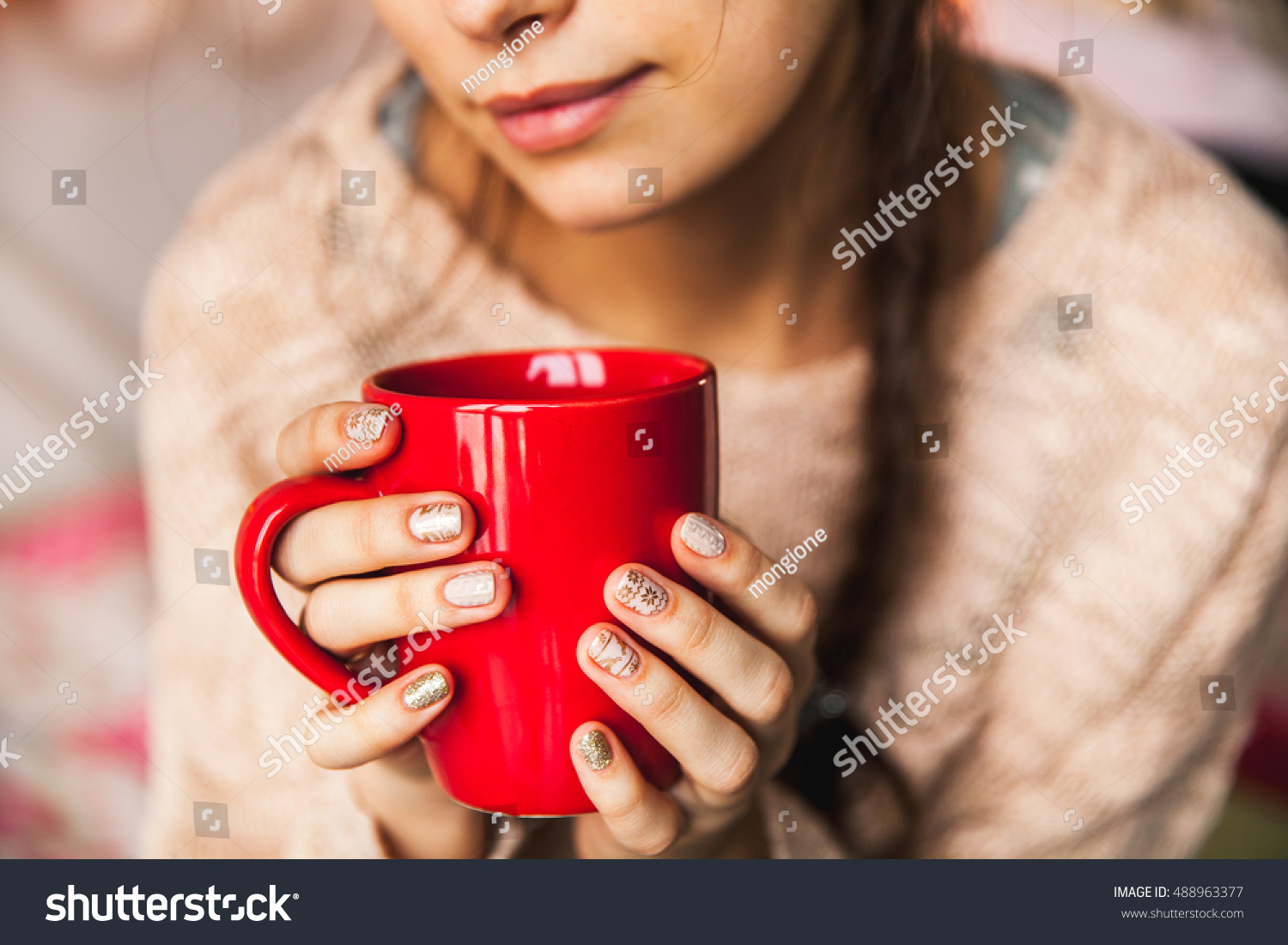 Woman's hand holding a red cup of coffee With a beautiful winter manicure Drink fashion morning