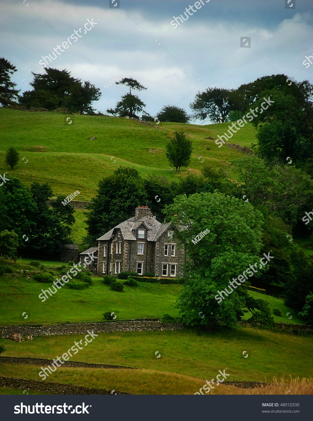 Stone Farmhouse Set In The English Countryside With Rolling Green Hills And Fences