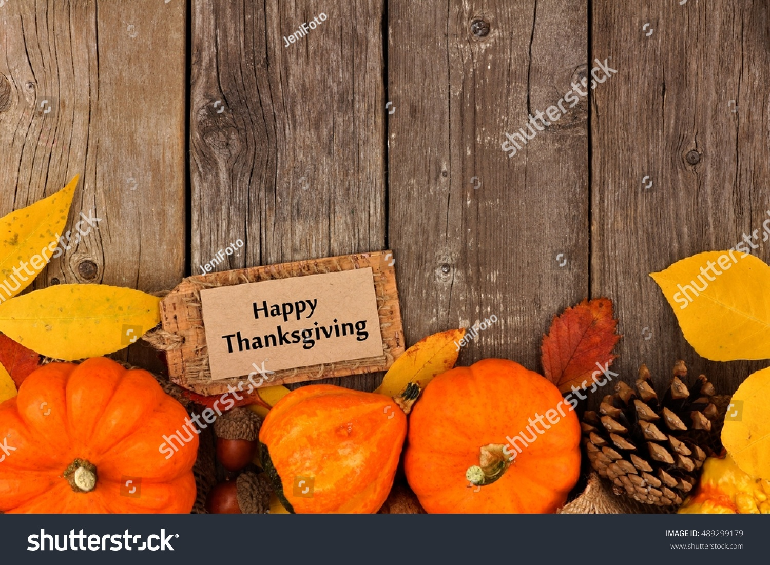 Happy Thanksgiving Gift Tag With Bottom Border Of Colorful Leaves And Pumpkins Over A Rustic Wood