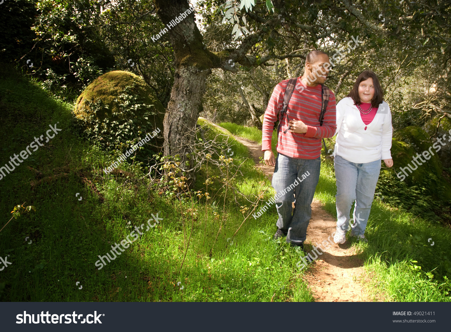 Photo of a young man walking with his visually impaired friend on a forest path using the sighted guide techniques. Image courtesy: Google