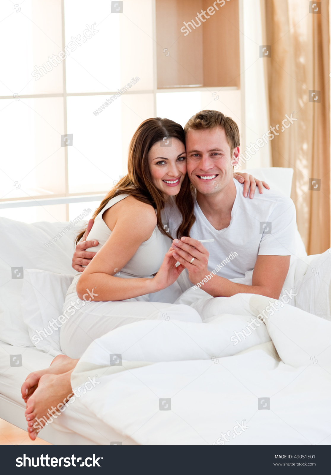 Romantic couple finding out results of a pregnancy test in their bedroom. Romantic Couple Finding Out Results Pregnancy Stock Photo 49051501