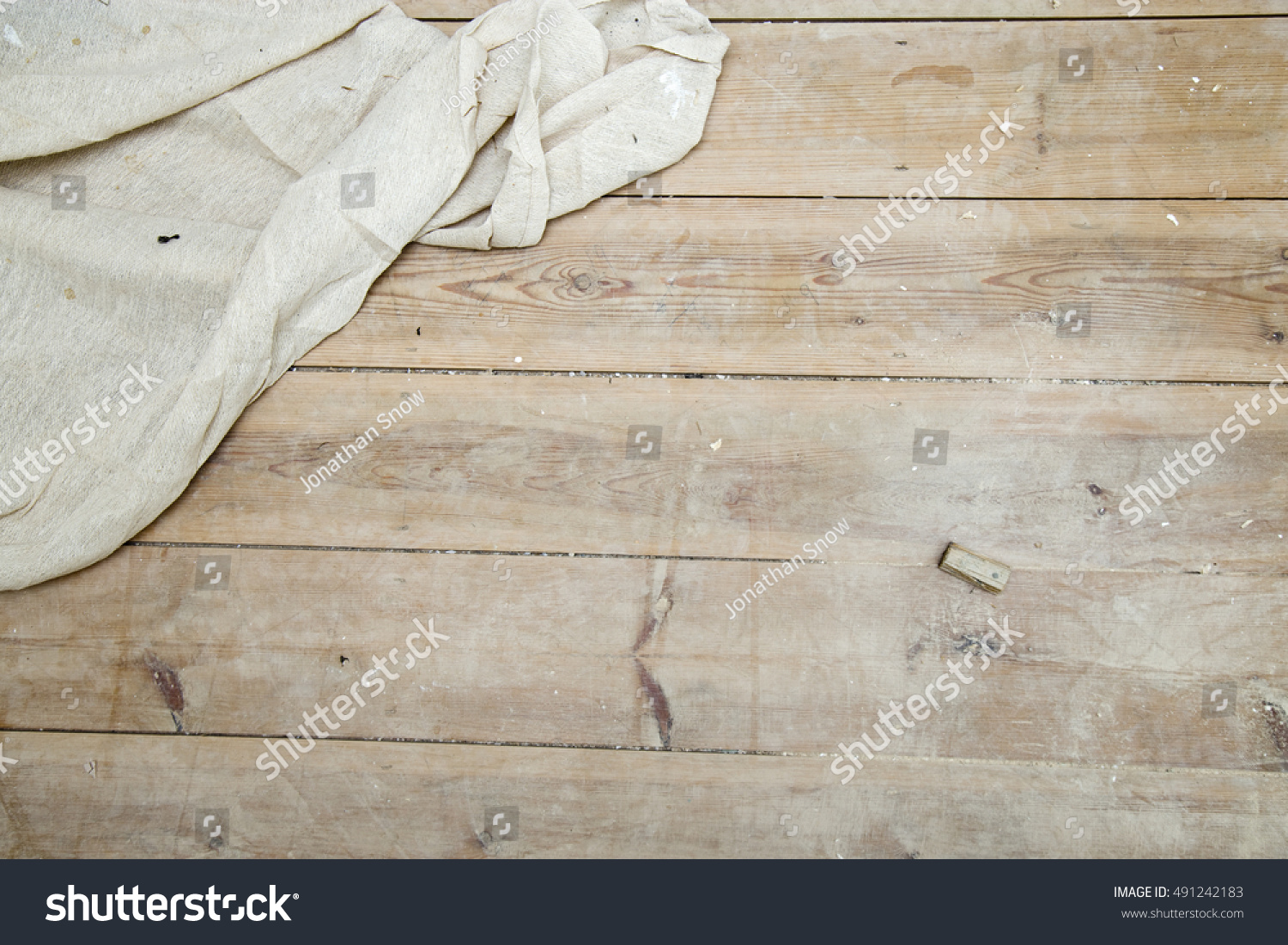 a white fabric dust sheet on an exposed wooden floor