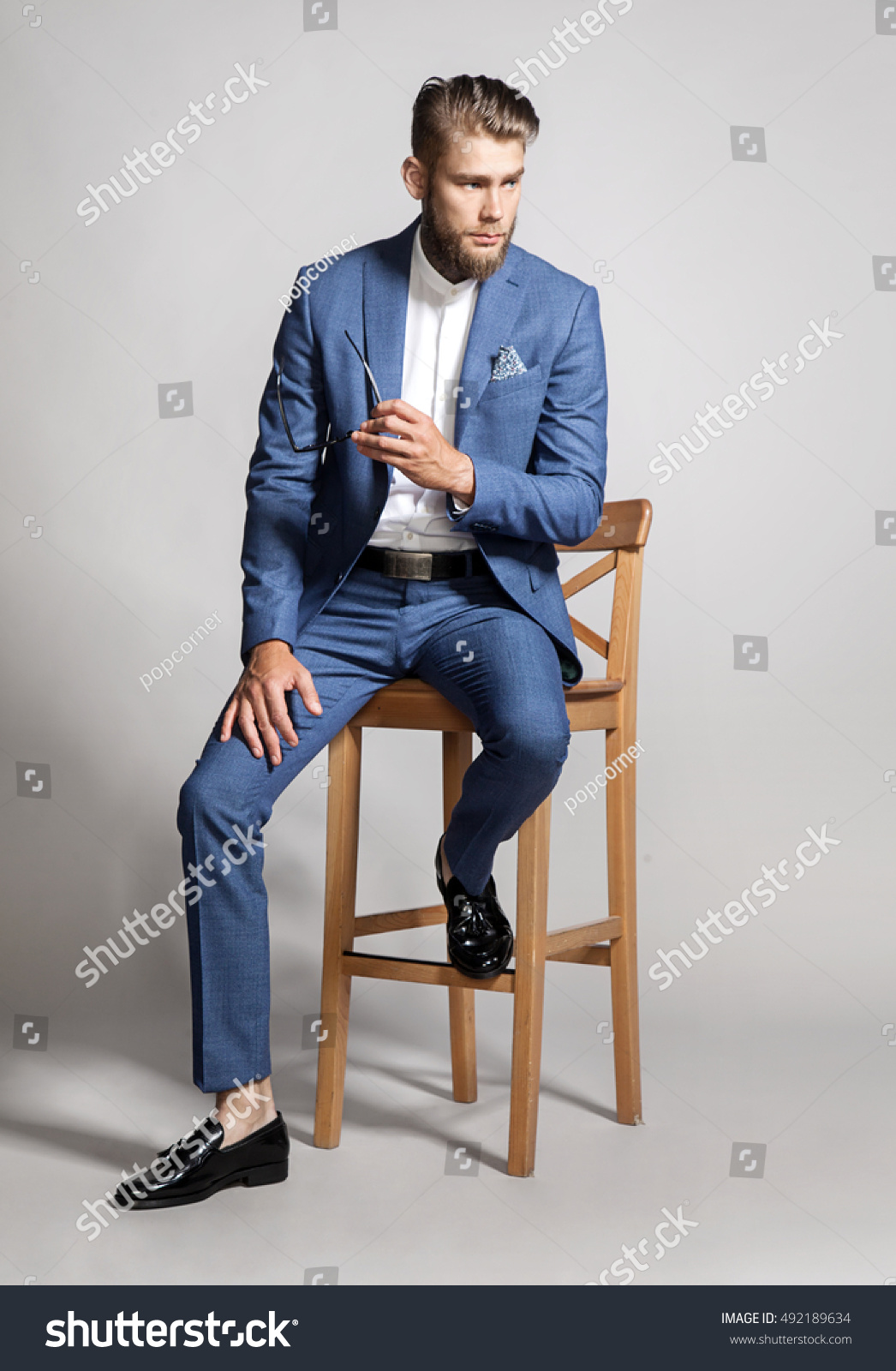 young handsome man suit sitting on stock photo 492189634