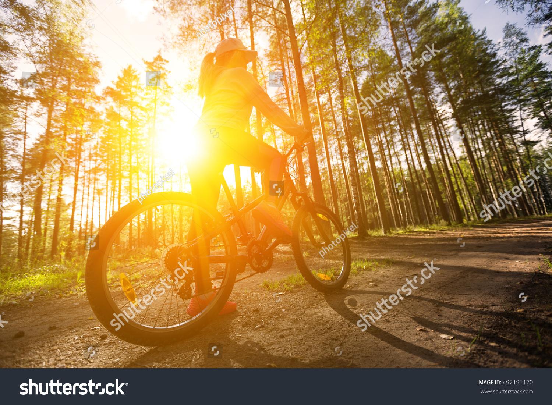 Woman Riding Mountain Bicycle Along Path Stock Photo