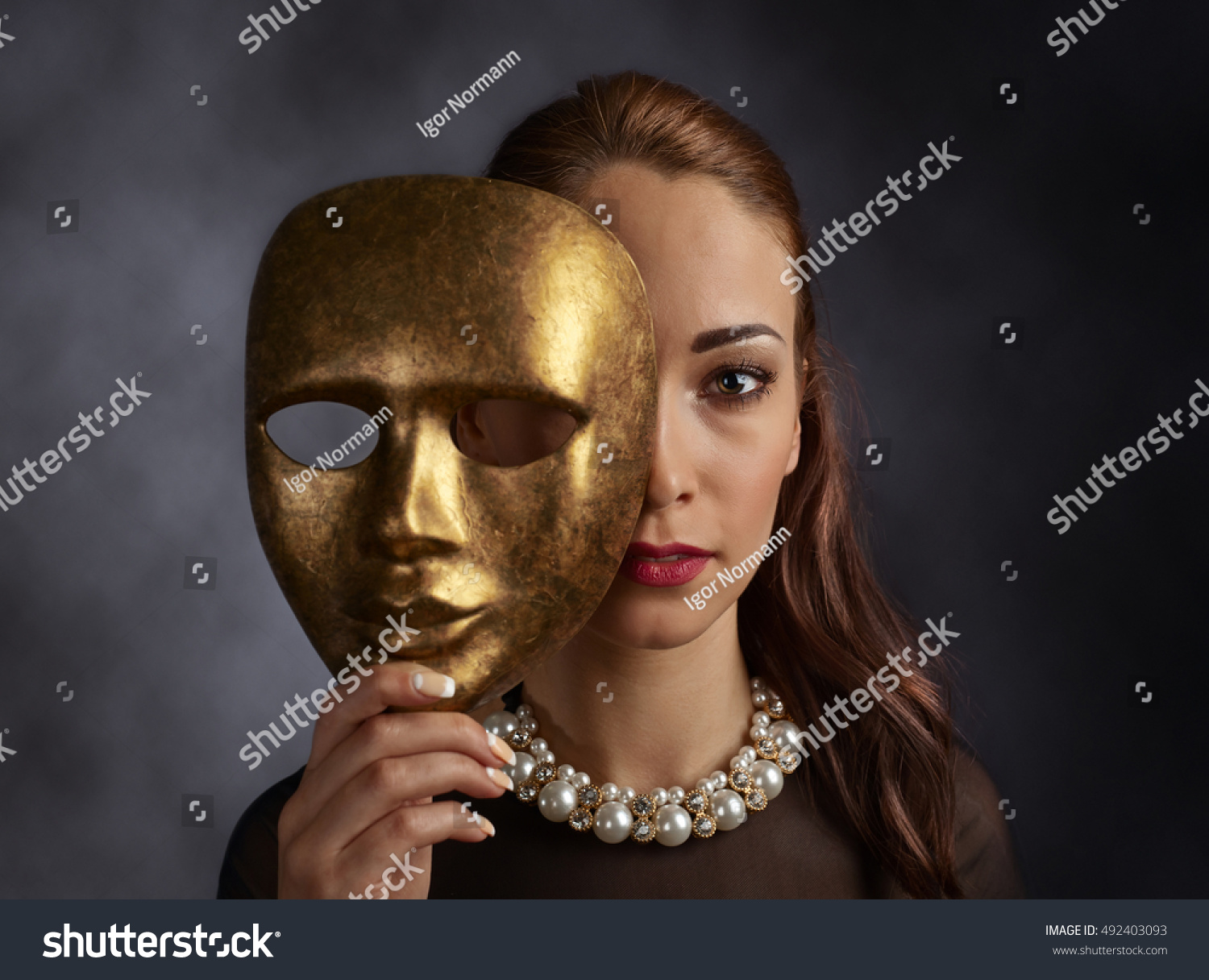 Beautiful Woman In A Black Dress With A Pearl Necklace And Old Mask