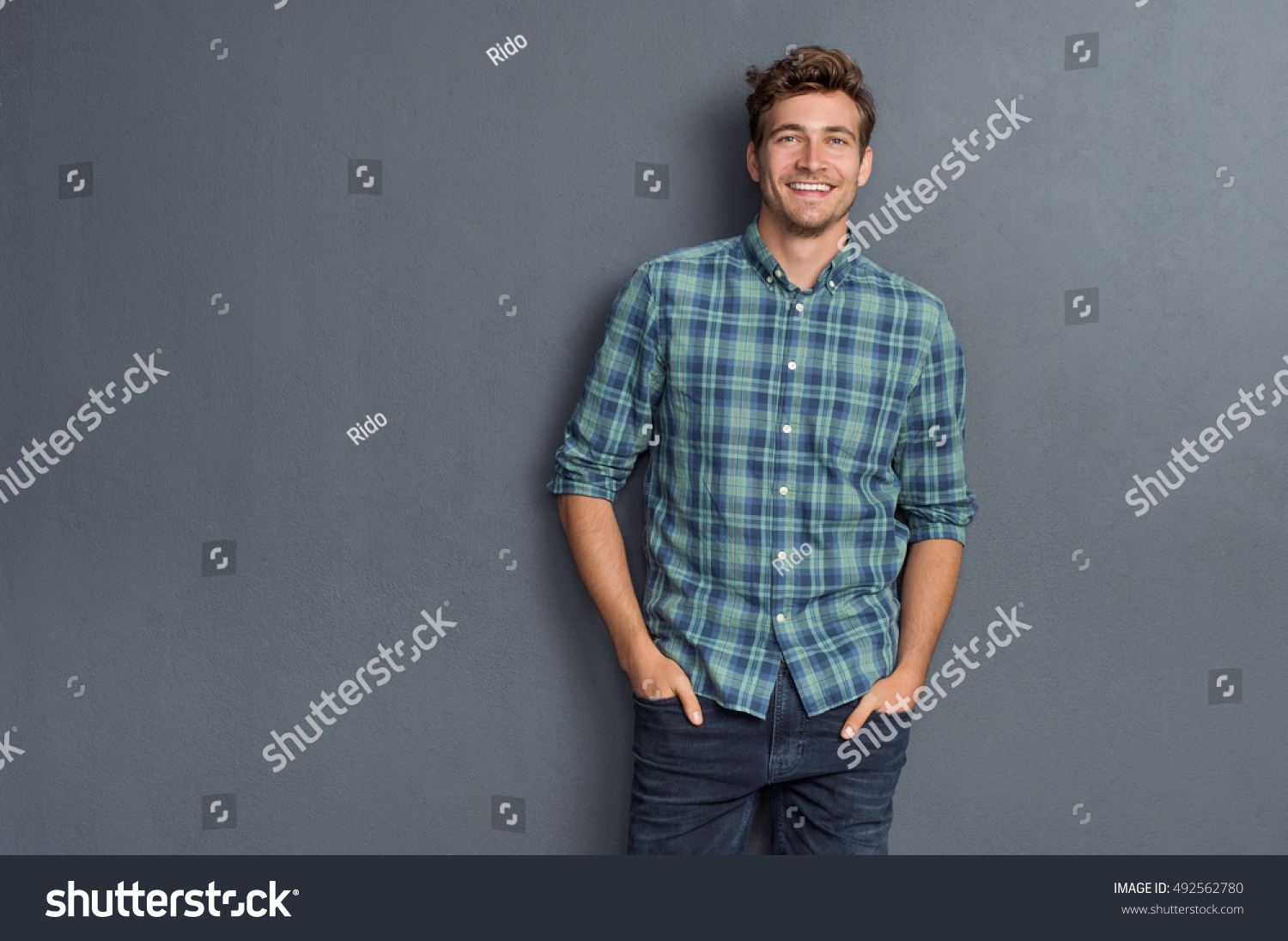 Handsome young man on grey background looking at camera. Portrait of laughing young man with hands in pockets leaning against grey wall. Happy guy smiling. #492562780