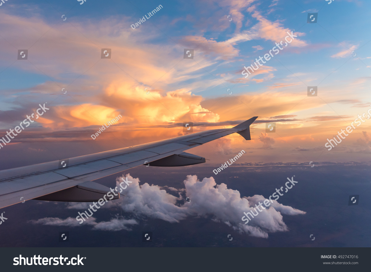 Aerial view of airplane wing with a colorful sunset sky on a partly cloudy day flying towards Fort Lauderdale, Florida, from the west coast.