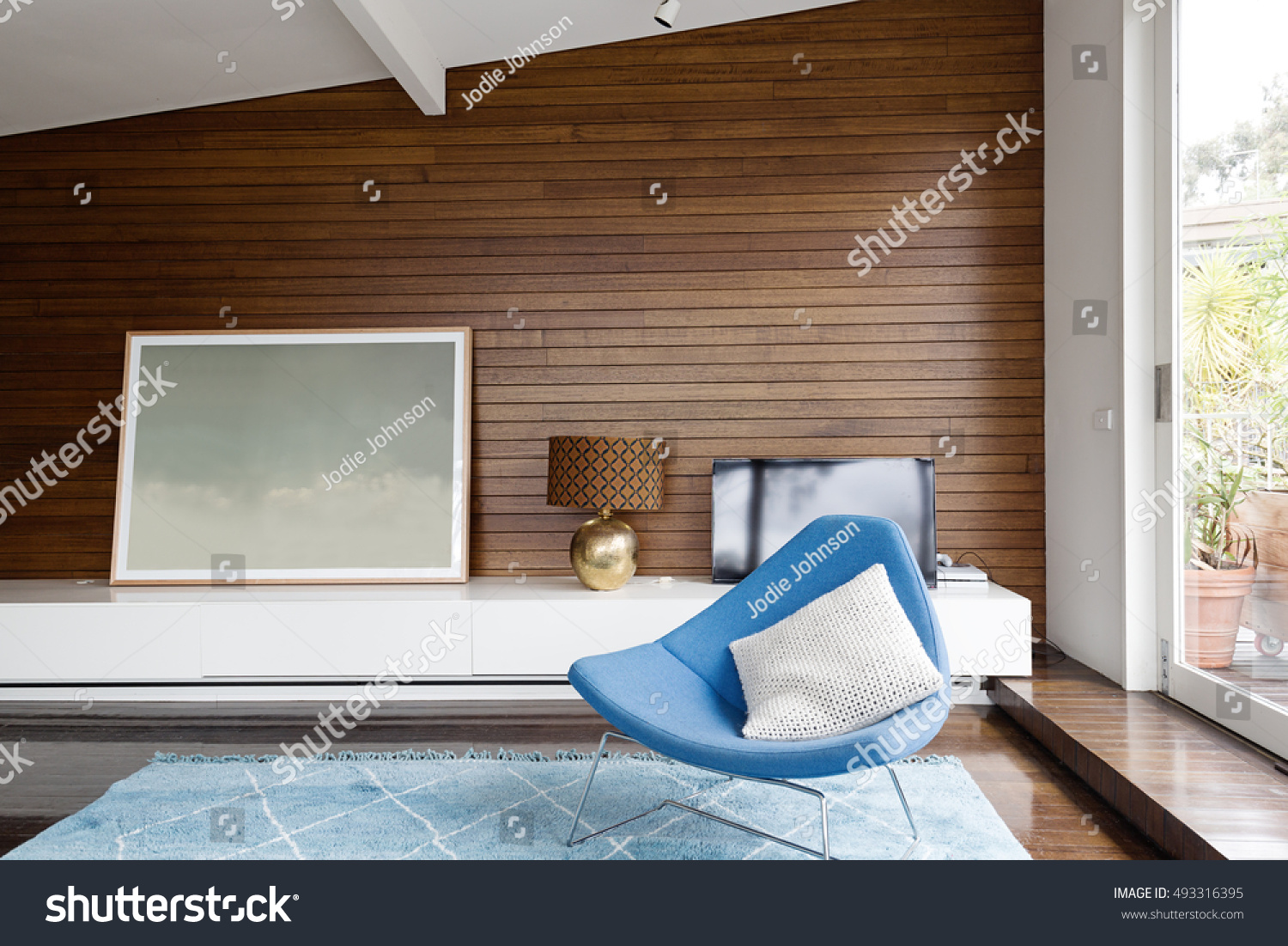 Horizontal wood panelling and blue occasional chair in mid century modern  living room. Horizontal Wood Panelling Blue Occasional Chair Stock Photo