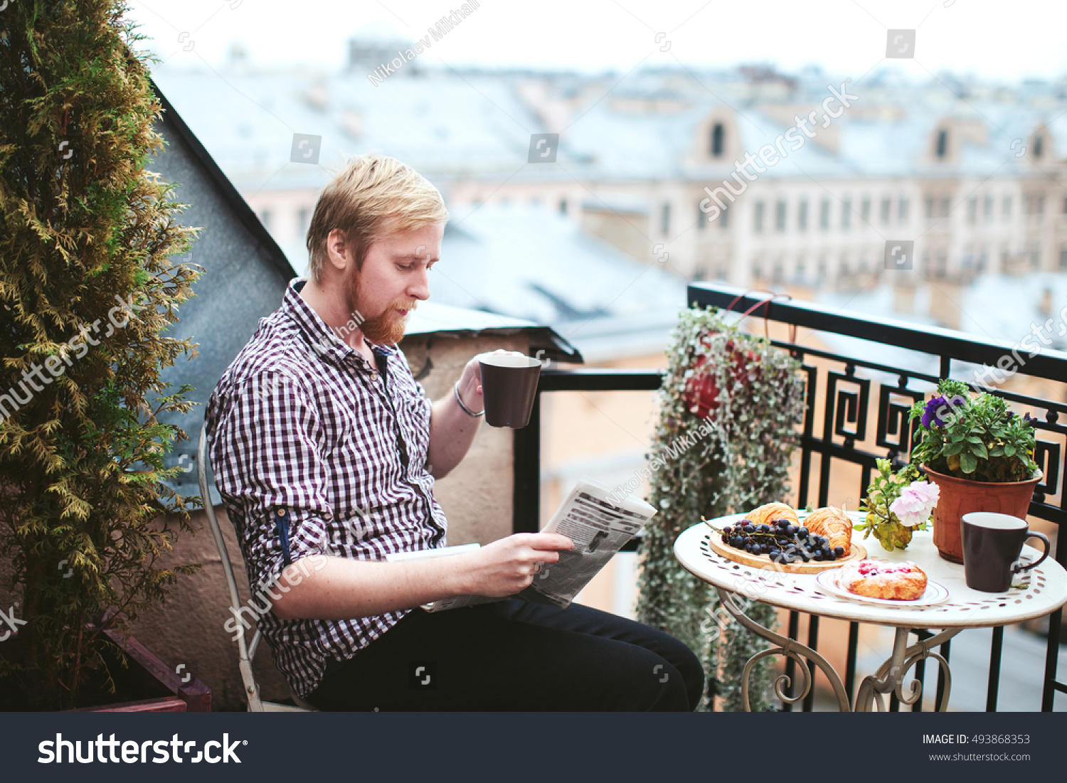 Man cup coffee reading newspaper on stock photo 493868353 for Balcony overlooking city