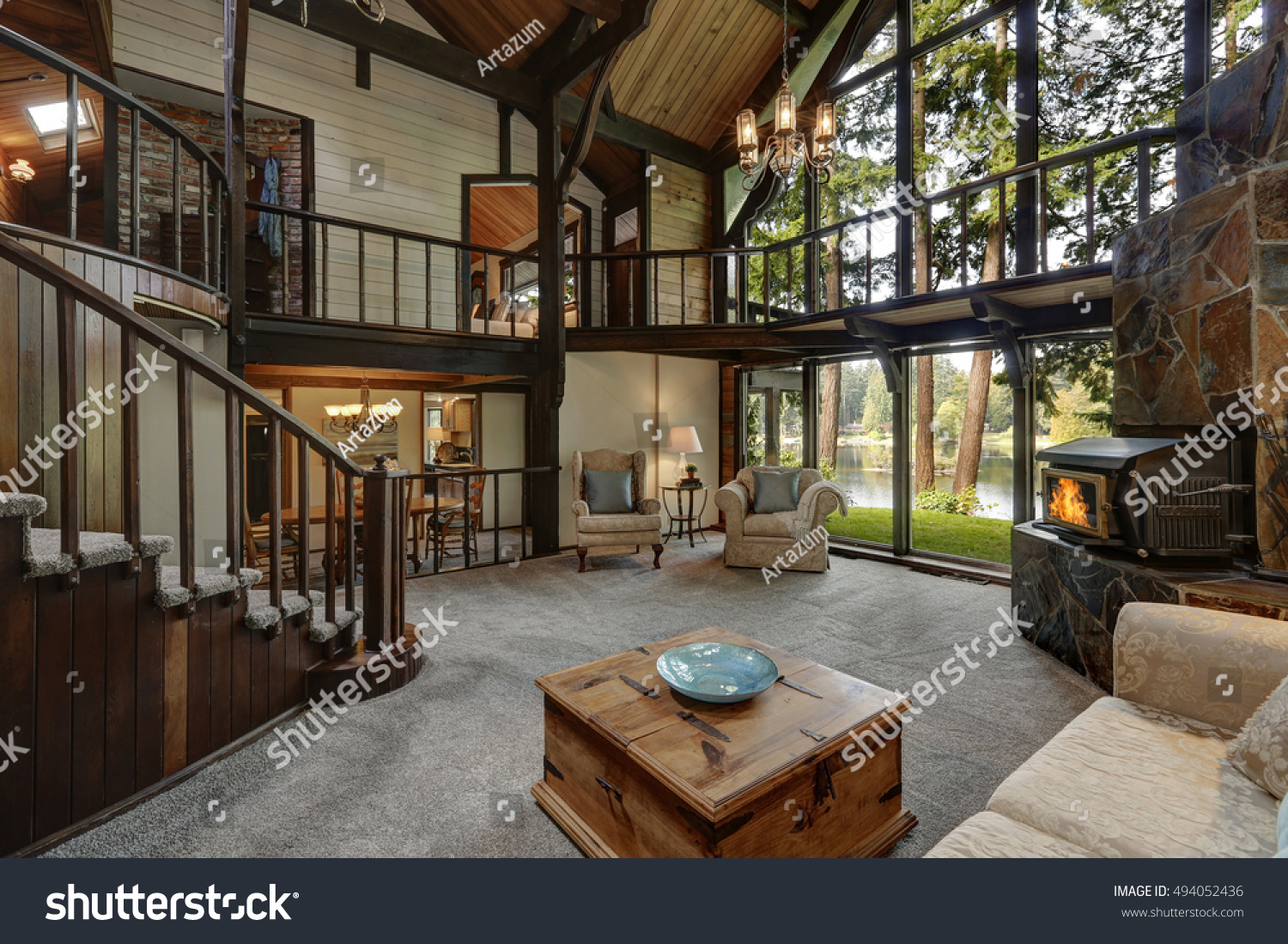 Modern wooden cottage house interior with living room close up Gorgeous fireplace with natural stone tile trim and large glass wall Northwest USA