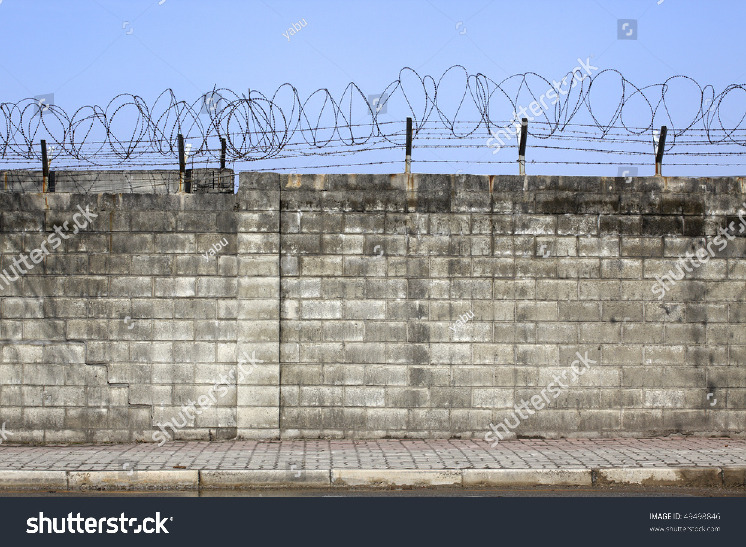 stock-photo-brick-wall-with-barbed-wire-49498846.jpg