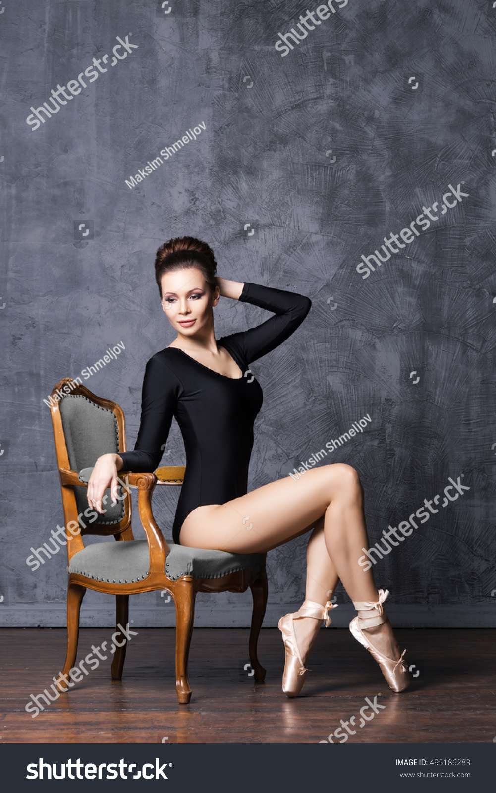 ea72fc61c739 Young and beautiful ballerina with a perfect body sitting on a retro  armchair.