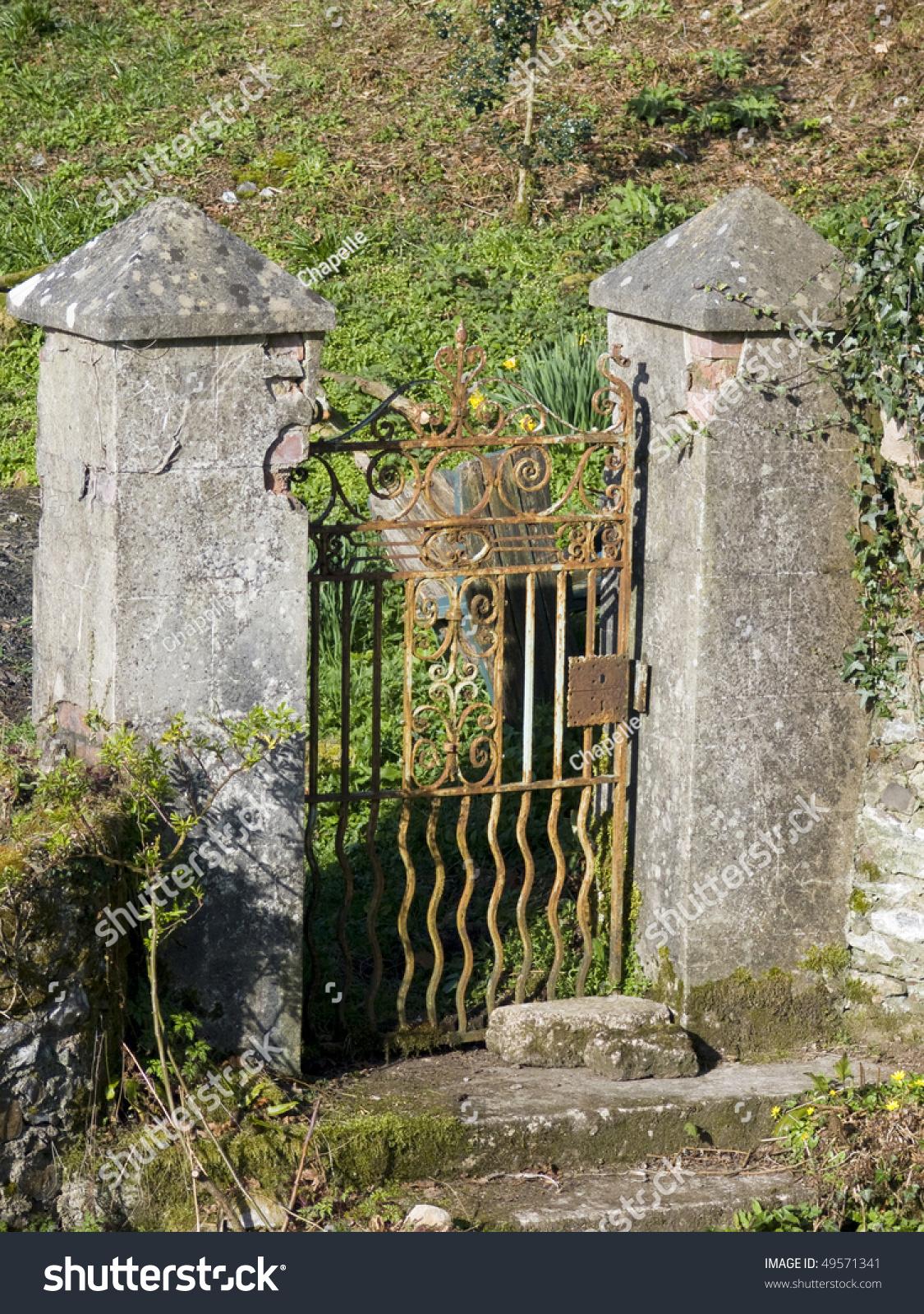 Old Stone Pillars : Old rusting fancy iron gate between decaying stone pillars