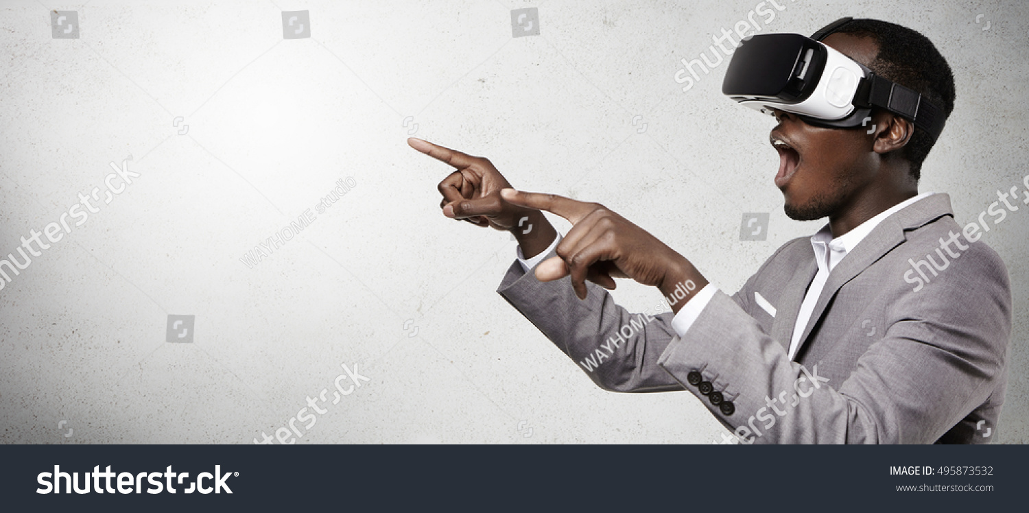 Headshot of excited dark-skinned businessman experiencing virtual reality using 3D headset gesturing as if watching something astonishing opening his mouth wide open and pointing with his fingers