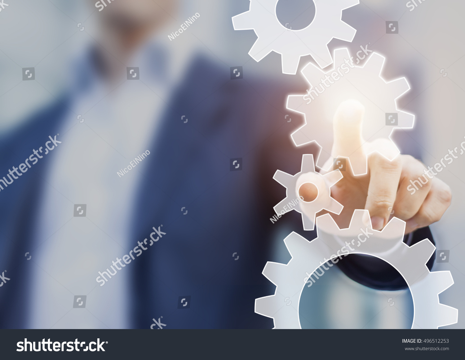 Business robotic process automation and workflow improvement concept represented by a businessman touching a cogwheel connected with other gears #496512253