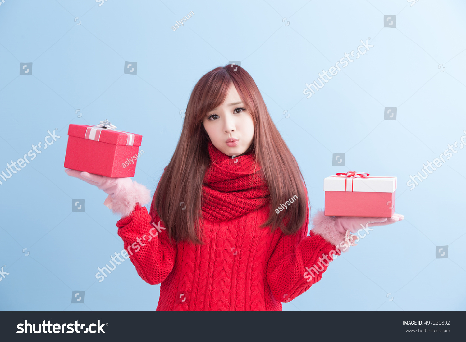 beauty woamn take gift and smile to you in christmas isolated on blue background asian