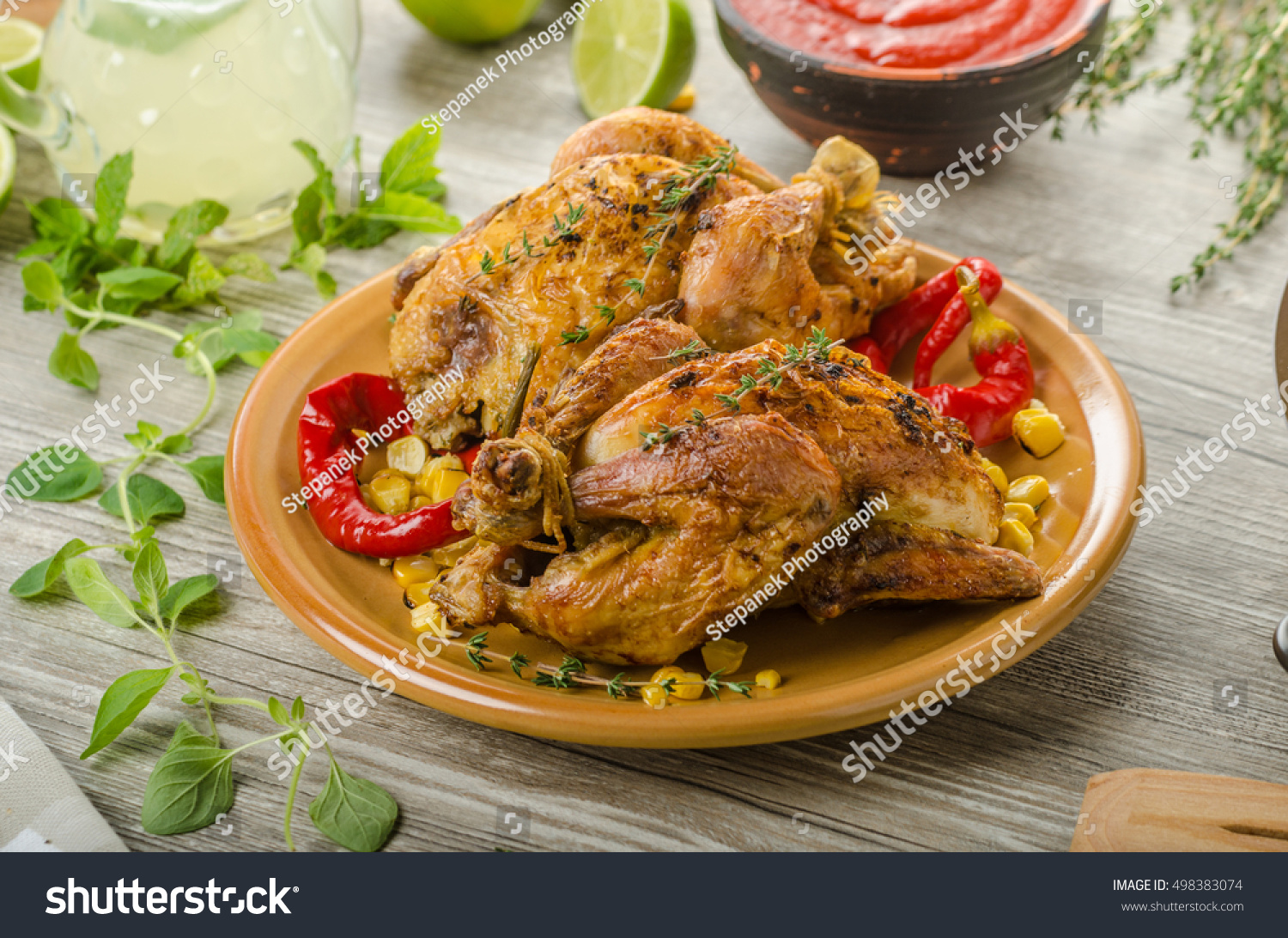 Roasted french baby chicken coquelet hebs foto de stock libre de roasted french baby chicken coquelet with hebs and grilled corn fresh lime lemonade forumfinder Choice Image